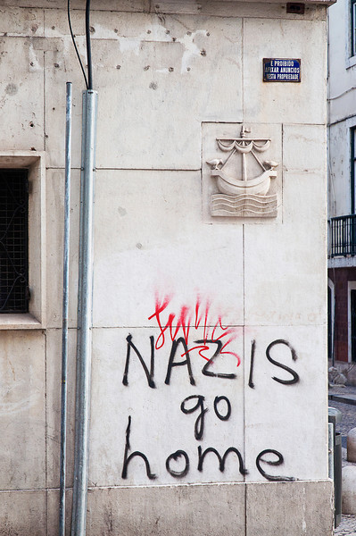 Although the public is abjured not to affix announcements on this building per the enameled sign at top right, one dauntless, English-speaking defender of liberalism was not swayed. How many english-speaking Nazis actually inhabit Lisbon feeds an early morning street photographer's wonderment.