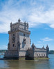 The Torre de Belem -- Belem Tower -- was built for harbor defense in the early 16th century and is a prominent example of the Portuguese Manueline style, but it also incorporates hints of other architectural styles. <br /> <br /> The structure was built from the unique local lioz limestone and is composed of a bastion and the 30 m (100 foot) four story tower. <br /> <br /> Local guides and books incorrectly state that the tower was built in the middle of the Tagus and now sits near the shore because the river was redirected after the 1755 Lisbon earthquake. In fact, the tower was built on a small basaltic island in the Tagus River near the Lisbon shore which has since crept out to meet the tower.