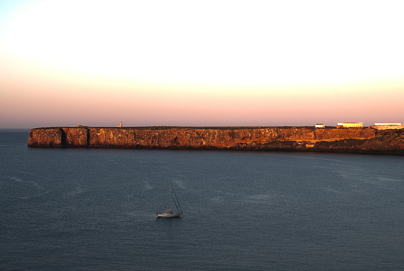 "Looking east at sunrise across the Bay of Sagres to Cape Sagres which has the un-documented reputation of being the spot where the Infante Dom Henrique -- aka Prince Henry the Navigator -- established his school of navigation, the Cape Canaveral of the Age of Discovery.<br /> <br /> An equally plausible, but no better documented legend has it in Lisbon.<br /> <br /> Contemporary accounts make it clear that the Infante lived here and had a substantial complex for some purpose here in the 15th century.<br /> <br /> The name itself derives from the Latin ""sacra"" or holy; the vicinity of Sagres Point and Cape St. Vincent has been used for religious purposes since Neolithic times as the many standing menhirs near Vila do Bispo a few miles away attest."