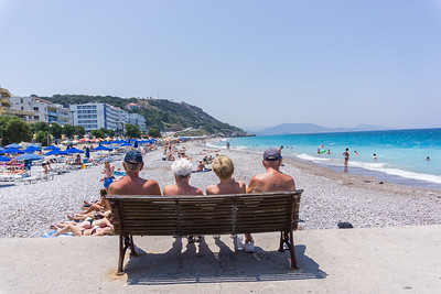 June 2019 2 men and 2 women sit and watch the beachgoers at Elli Beach, Rhodes, Greece