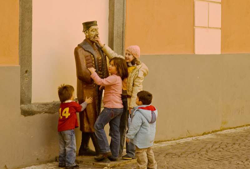 Children harassing a statue in the main square