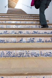 The risers of the stairs are covered in tiles with bullfighting scenes.