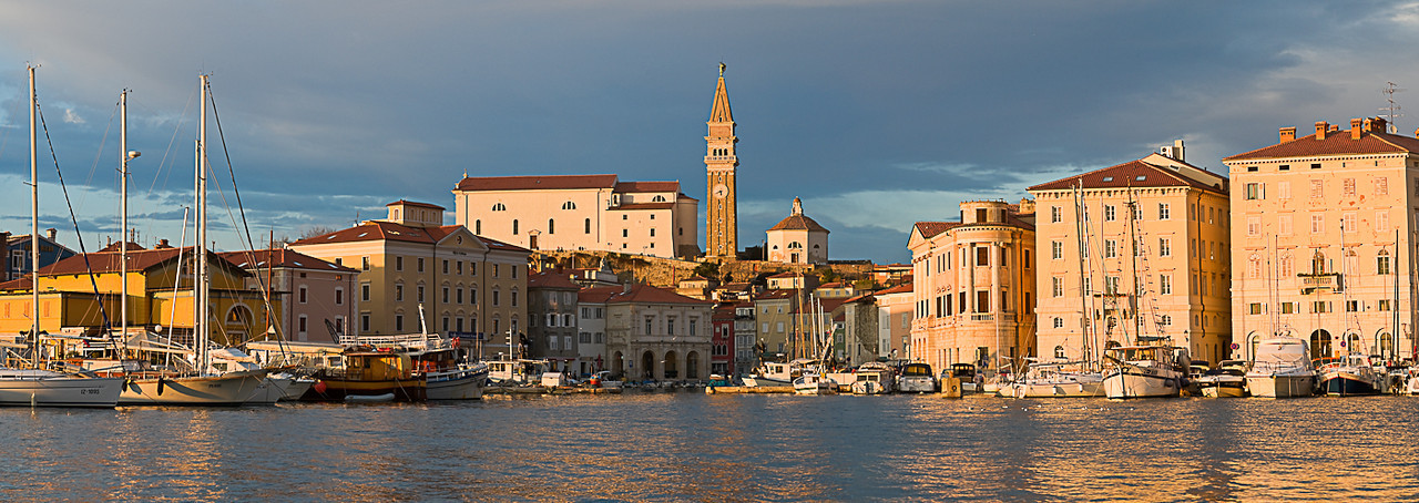 Waterfront buildings clock tower and church taken at t night at Piran harbour, Slovenia