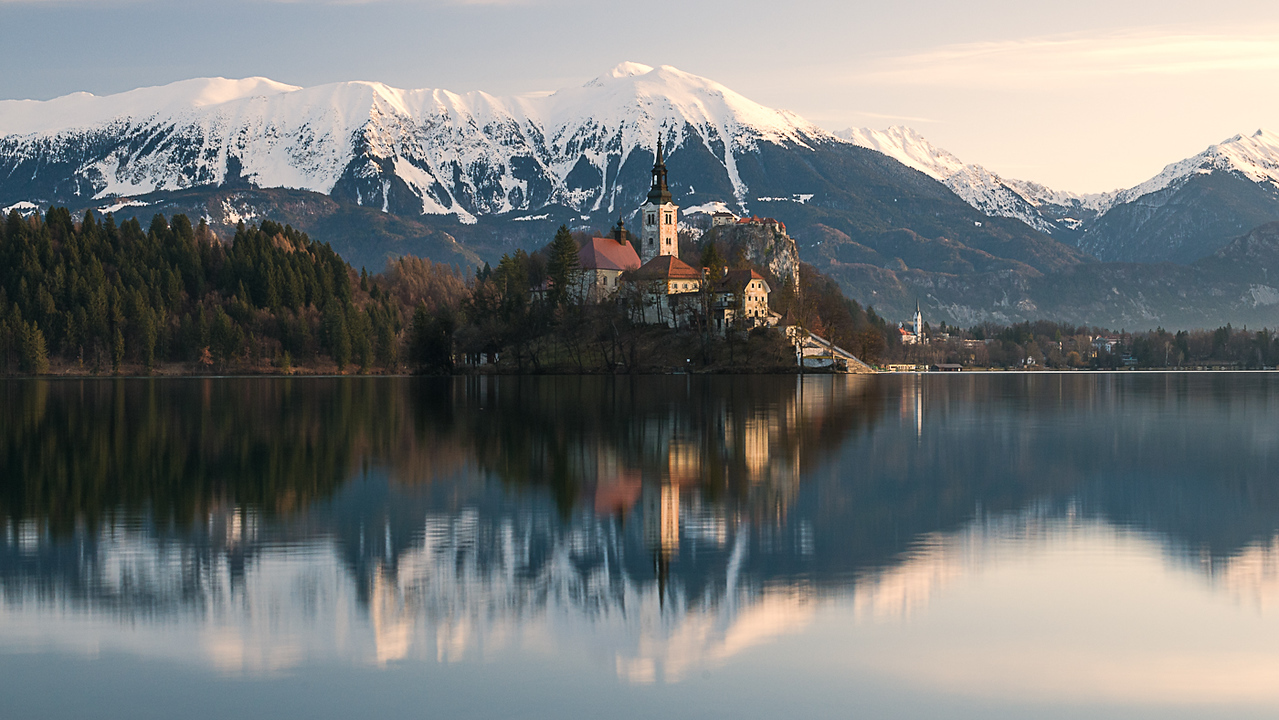 View towards Lake Bled in Slovenia at dawn with Bled Island and the Pilgrimage Church of the Assumption of Mary with the Julian Alps in the background