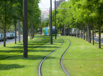 Bilbao, Spain A Euskotren Tranbia train by BasqueRailways travels along the rail line in Bilbao's Abandoibarra green space.