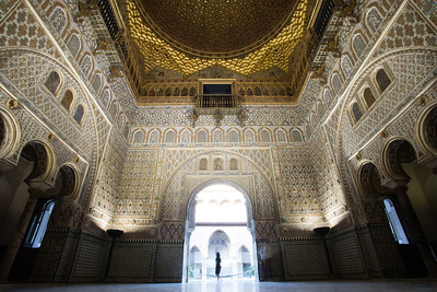 A female tourist poses at the entrance to the Salón de Embajadores (Hall of Ambassadors) of the Royal Palace in Seville, Spain.