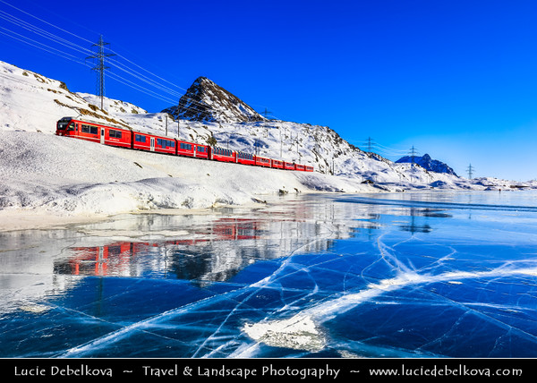 Europe - Switzerland - Swiss - Graubünden Canton - Grisons - Alps - Alpen - Alpi - Alpes - Great Mountain Range in Europe - Lago Bianco - White Lake - Iconic water reservoir at Bernina pass - Alpine mountain lake at 2,253 metres above sea level - Winter snowy landscape with frozen lake - Ospizio Bernina (Rhaetian Railway station) - Iconic red train