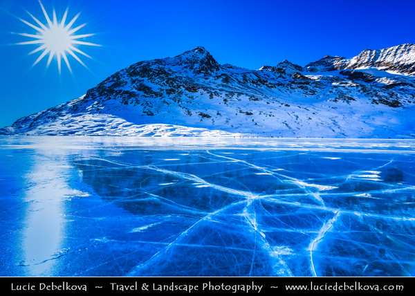 Europe - Switzerland - Swiss - Graubünden Canton - Grisons - Alps - Alpen - Alpi - Alpes - Great Mountain Range in Europe - Lago Bianco - White Lake - Iconic water reservoir at Bernina pass - Alpine mountain lake at 2,253 metres above sea level - Winter snowy landscape with deep frozen lake and long ice cracks