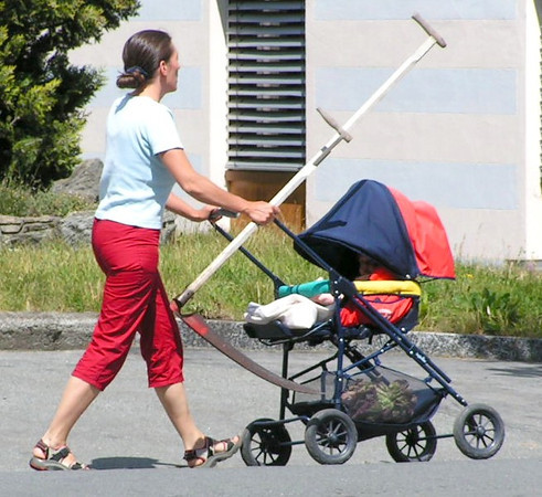 Woman pushing a pram carrying a hay sythe