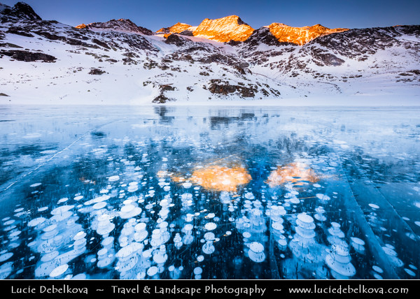 Europe - Switzerland - Swiss - Graubünden Canton - Grisons - Alps - Alpen - Alpi - Alpes - Great Mountain Range in Europe - Lago Bianco - White Lake - Iconic water reservoir at Bernina pass - Alpine mountain lake at 2,253 metres above sea level - Winter snowy landscape with deep frozen lake and surreal frozen bubbles