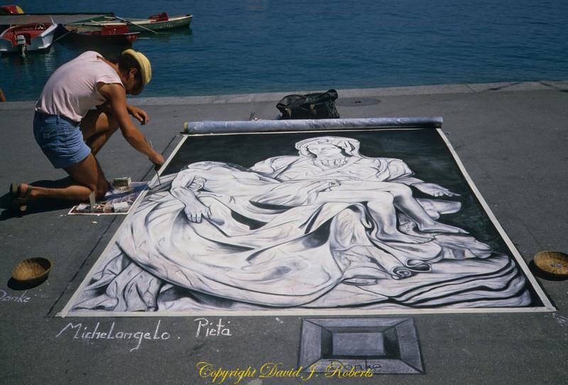 Chalk artist on waterfront sidewalk in Lucern Switzerland