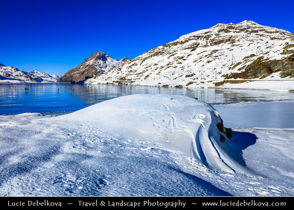 Europe - Switzerland - Swiss - Graubünden Canton - Grisons - Alps - Alpen - Alpi - Alpes - Great Mountain Range in Europe - Lago Bianco - White Lake - Iconic water reservoir at Bernina pass - Alpine mountain lake at 2,253 metres above sea level - Winter snowy landscape with deep frozen lake