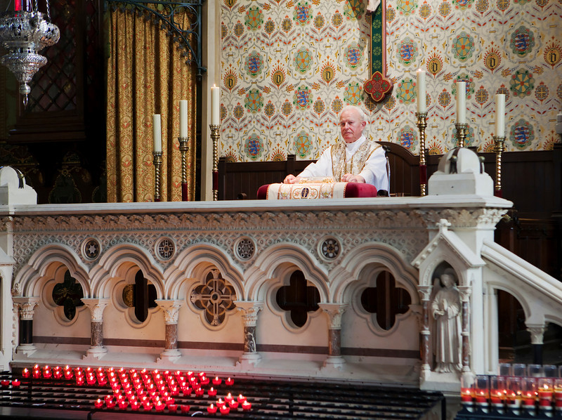 Priest preparing for a service at the Chapel of the Holy Blood in Bruges, Belgium. Between his hands on the cushion is a religious relic, enclosed in glass, that is used as part of the service.