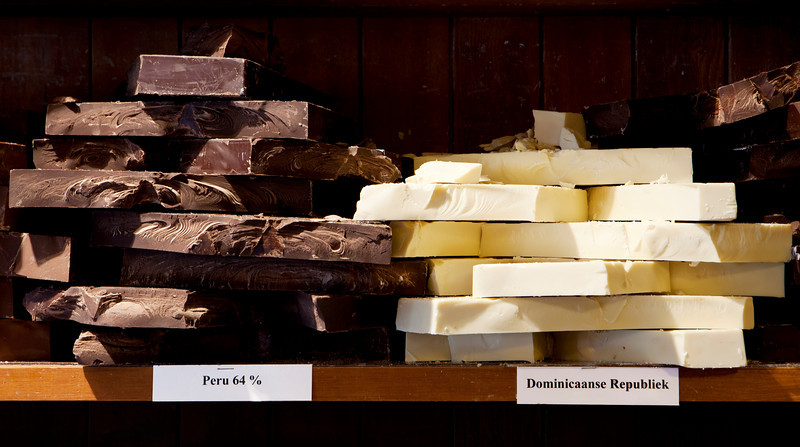 Chunks of white and dark chocolate from different points of origin are for sale in a candy store.
