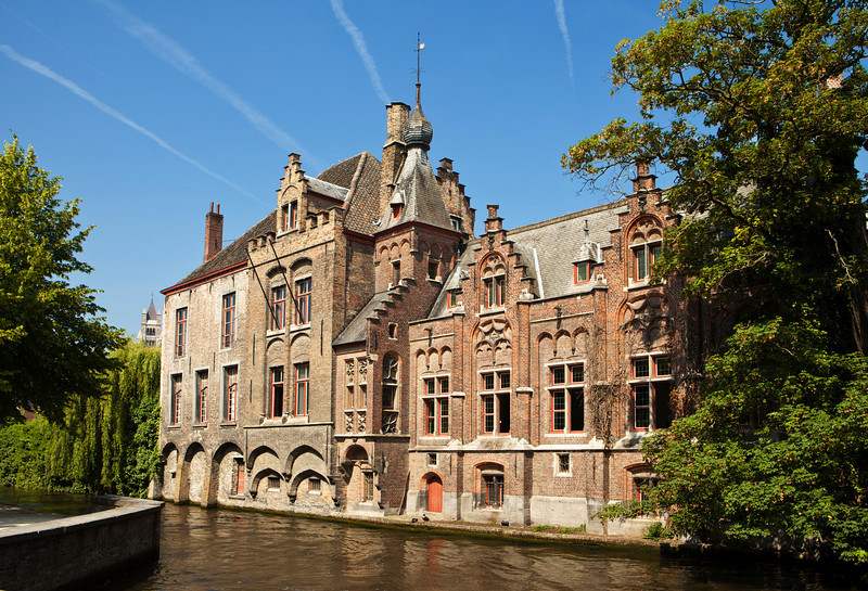 A classic old landmark brick building near one of the canals in Bruges, Belgium. The aircraft contrails in the sky lead directly to the peak of the roof.