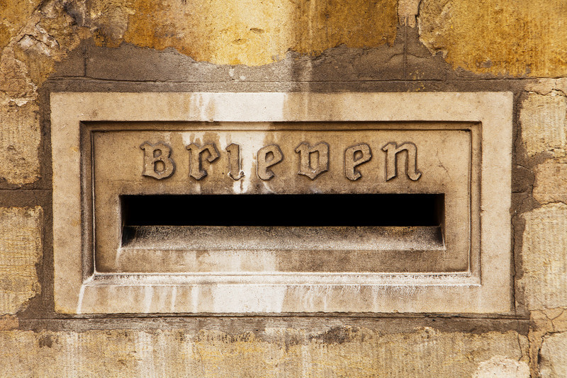 Architectural detail of a letter slot for letters, or brieven, is located on the exterior stone wall of the town hall in the city of Bruges in Belgium.