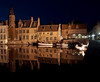 A view of some of the historic buildings on the canal in Bruges at night. The boats in the water are used for tourists during the daytime