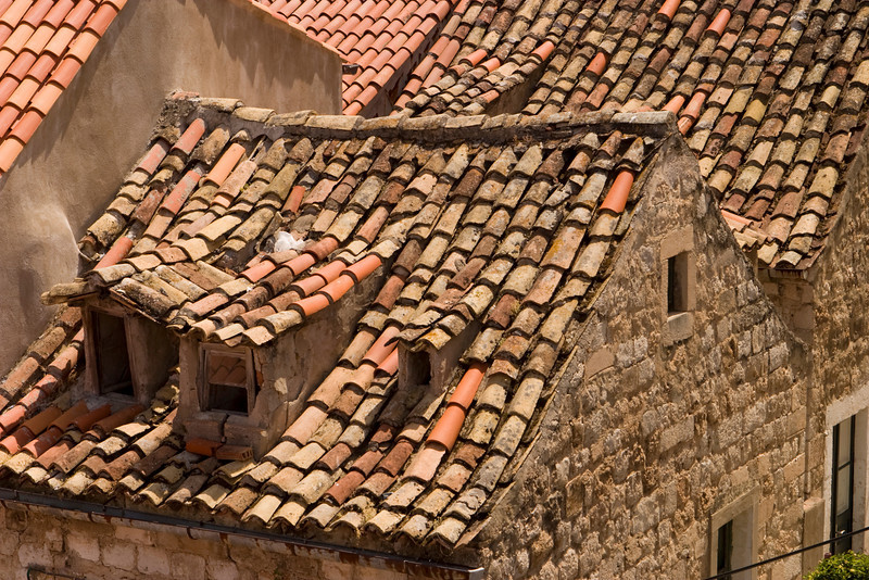 Old red tile rooftops in Dubrovnik are uneven and show interesting character. These roofs show some patching after the city was shelled in the 1990s.