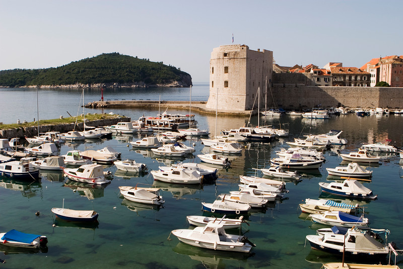 The main harbor next to the old town of Dubrovnik. The harbour, filled with boats, is surrounded by the old city walls and fortresses that protected the city.