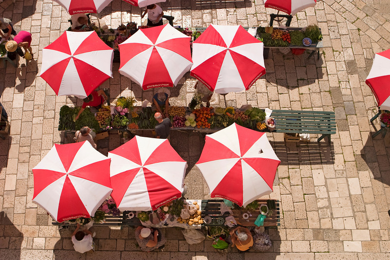 An aerial view of the local farmer's market (Sanitat) in Dubrovnik. The produce is all displayed on tables under the red and white umbrellas.
