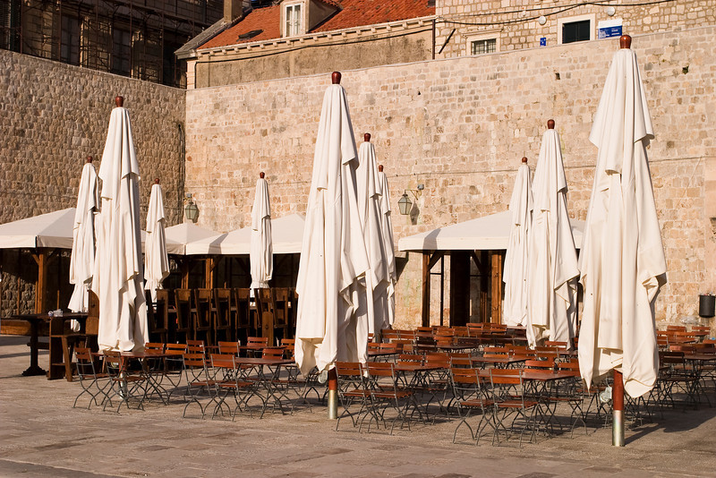A cafe in Dubrovnik, Croatia is waiting with empty tables and furled umbrellas for the first customers. It is located next to the harbor and old city stone walls.