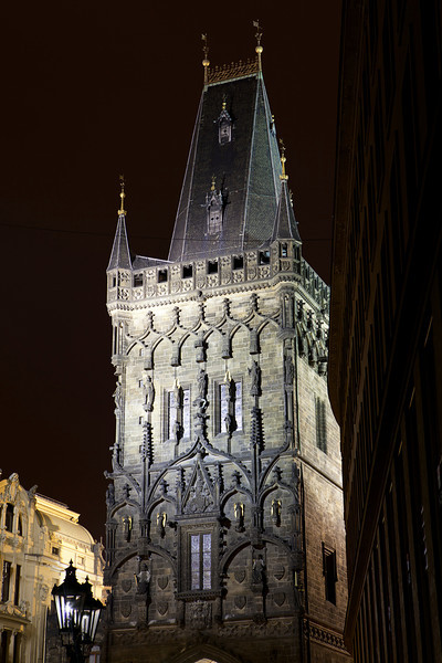 The landmark Powder Tower on the edge of the Old Town of Prague is illuminated at night with a spotlight.