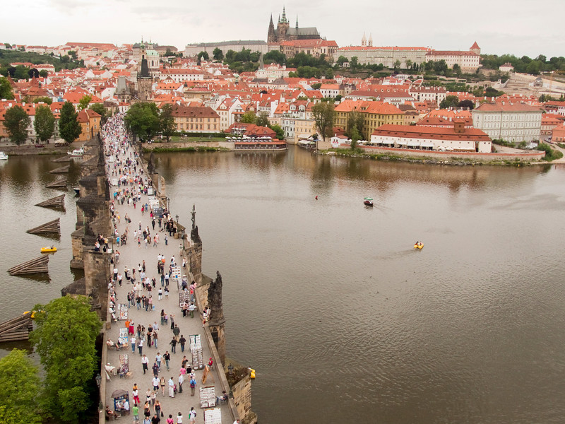 A view of Charles Bridge (Karluv Most) in Prague when it is crowded with throngs of tourists in the summer. This perspective is from one of the main bridge towers with a view that includes Hradcany castle and St. Vitus Cathedral on the skyline.