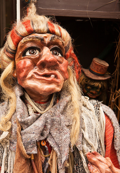 A puppet rendition of a witch is a caricature with a single tooth and dressed in rags. The detailed carved figure with wig and hand painted features is a traditional Czech craft style.