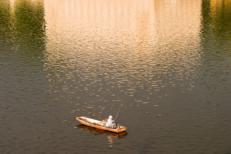 A lone fisherman is fishing from a boat in the Vltava River in Prague. On the water behind him is an almost impressionist golden reflection from a palace on the river bank.