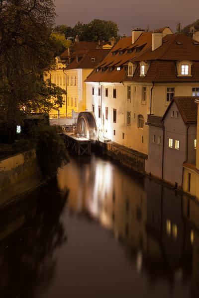 A night view of one of the canals in Prague as seen from the Charles Bridge. At the end, an old water wheel is slowly turning, creating a blur in the evening light.