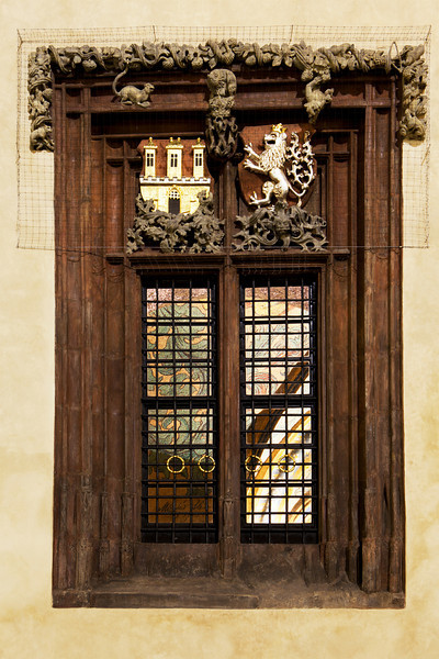 A window on the exterior of the City Hall building in Prague's Old Town main square. The castle and lion symbols represent Prague's history. The brighly painted interior is visible through the windowpanes.