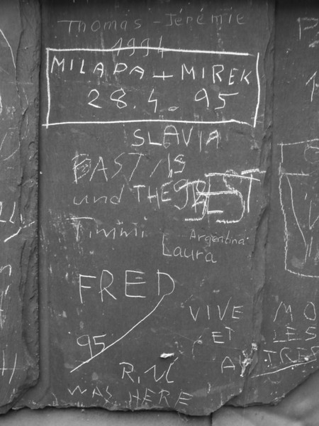 Slate roof shingles in Prague have been defaced by tourist graffiti over the years. (In black and white.)