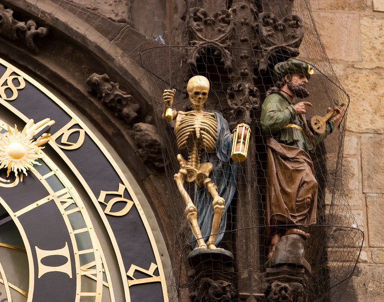 Prague's astronomical clock is a landmark. The clock face is surrounded by medieval sculptures including the skeleton that represents Death.