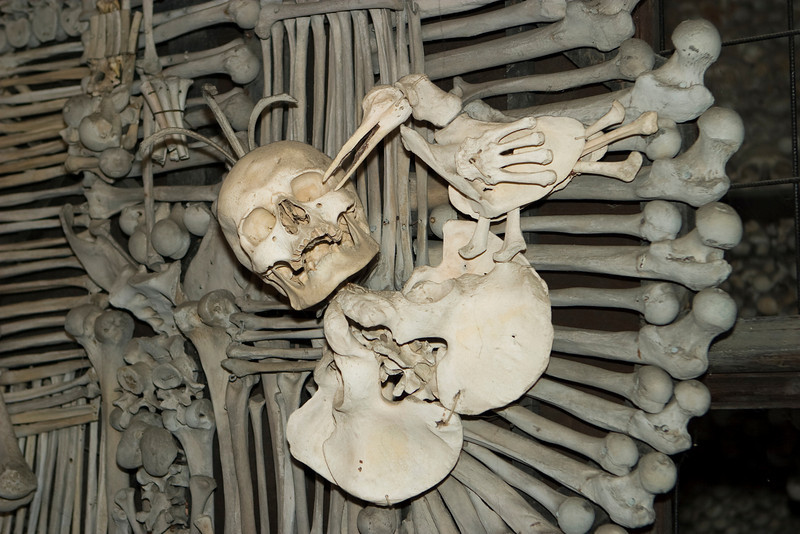 Detail view with a skeleton making a salute. This is one of the main ornamental works at the bone church in Kutna Hora. The All Saints church has thousands of skeletons in its four main crypts.