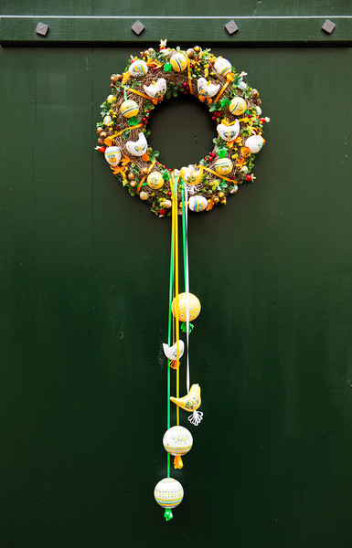 A traditional Czech wreath hanging on a green door. It is made with tree branches and filled with ornamental decorations such as birds, balls, ribbons, and more.