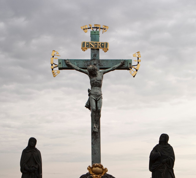 A statue of Jesus Christ on a crucifix with Hebrew letters on the ends. Two dark sculptures are silhouetted on either side.