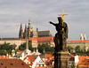 A view of Prague Castle from the Charles Bridge. In the foreground, a sculpture is holding a gold cross and is seemingly pointing a finger at the castle. A spot of early morning sunlight lighting the scene.