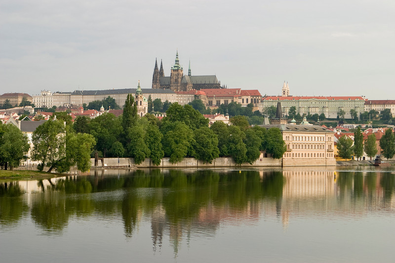 A scenic view of the Prague Castle and cathedral. Reflections of the scene are visible in the water on the Vltava River.