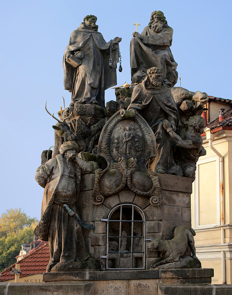 Statues of Saints John of Matha, Felix of Valois, and Ivan on the Charles Bridge in Prague. Designed in 1714, the sculpture honors the two founders of the Trinitarians, the order that supervised buying back and redeeming of Christians in captivity under Turks. The base depicts a cave with three chained Christians praying to the Lord for salvation. St. Ivan, the saint patron of Slavs was added to the group for unknown reasons.