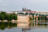 A single man rowing up the Vltava River in Prague with the Prague castle and cathedral in the background.