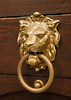 An old Czech door knocker in the form of a lion's head, worn shiny in places from being touched over the years.