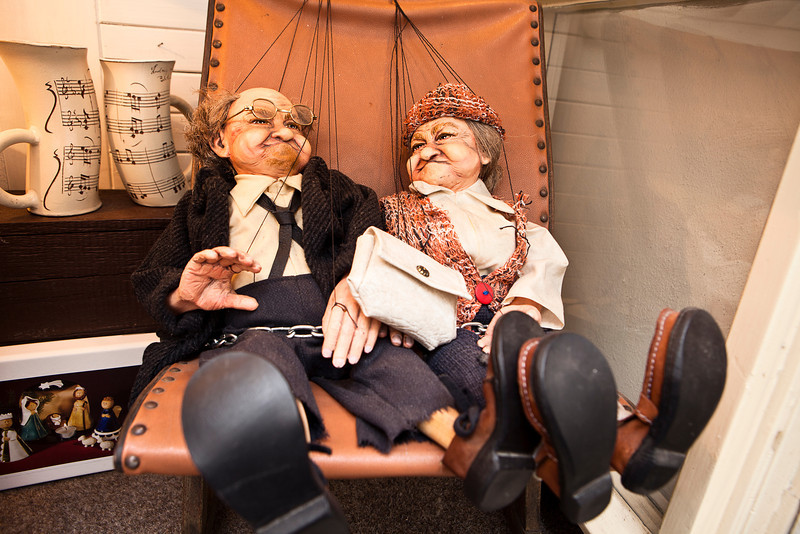 Two ornamental puppets or marionettes sit together and recline in a storefront window.