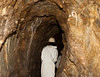 A person dressed in a white coat and helmet is walking through a  tunnel in an old medieval silver mine in the Czech Republic.
