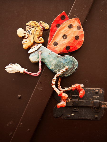 A mechanical caricature that is carved from wood adorns a door in Prague. This fairy godmother with ladybug has legs and wings which move as the door moves.