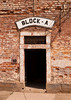 The entrance door to the cells in Block A at the Theresienstadt concentration camp in what is now the Czech Republic. The dark black opening, framed by red bricks, is an ominous sign of what took place behind the door.