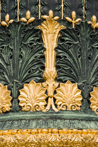 A detail of the base of a lamp post in Paris, France that shows the ornate decorations in bronze and gold paint.