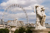 The ferris wheel in the center of Paris with a statue of Spartacus in the foreground.