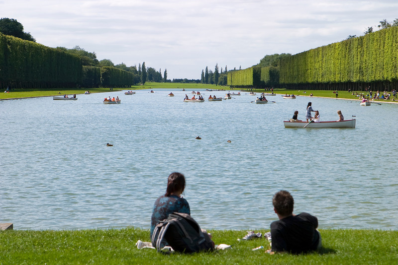 A couple is lying by the side of the lake at Versailles watching many small rowboats between the gardens.