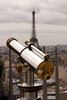 A bright and shiny telescope on the Arc de Triomphe in Paris with the Eiffel Tower in the background.