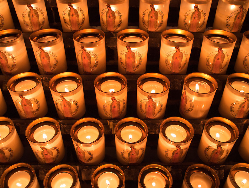 A bank of devotional prayer candles are lit and providing illumination at the cathedral of Notre Dame de Paris.